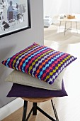 A colourful, knitted, homemade, striped cushion cover