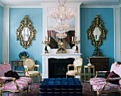 Rococo salon with Louis XVI sofas and armchairs and two mirrored sconces on blue wall