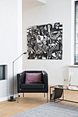 Black leather armchair and standard lamp below black and white modern artwork in corner