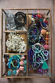 Various bead necklaces in open-topped, glass jewellery box