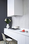 Minimalist kitchen counter with classic chair in front of gas hob and extractor hood on exposed concrete wall