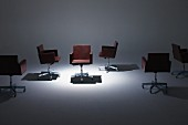 Brown leather swivel chairs under spotlight