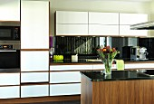 Elegant walnut kitchen with white front panels and black granite worksurface; island counter in foreground