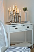 Lit candles in silver candlesticks on tray on vintage table