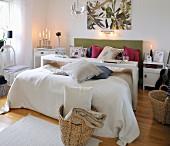 Schmales Tischgestell über Doppelbett mit Zierkissen, brennende Kerzen und geflochtene Körbe