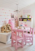 Pink children's table and soft toys in front of heart-patterned wallpaper