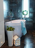 House-shaped lantern and floor vase in front of designer bathtub in dark-tiled bathroom