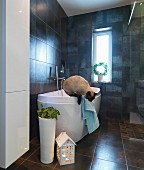 House-shaped lantern and floor vase in front of designer bathtub in dark-tiled bathroom; cat jumping down from edge of bath