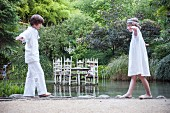 Two children balancing along edge of pond in front of table standing in water