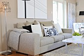 Ecru sofa with scatter cushions next to retro standard lamp, modern coffee table and rug in contemporary living room