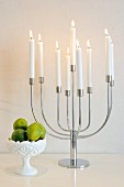 Lit, white candles in multi-armed candelabra and small bowl of fruit