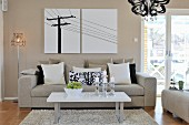 Coffee table on flokati-style rug in front of sofa with row of scatter cushions and retro standard lamp next to modern artwork on wall painted pale grey