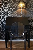Ghost chair in front of black, antique bureau with table lamp against black wallpaper with ornamental silver pattern