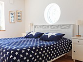 Porthole above double bed in Scandinavian bedroom with blue bedspread and pillows with pattern of stars
