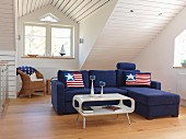 Blue sofa combination with stars and stripes cushions in front of wood-clad sloping ceiling with dormer window