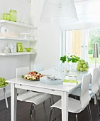White dining table and chairs below window next to crockery on floating shelves with green accents
