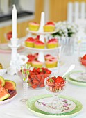 Table set with strawberries, candles and pastries on cake stand