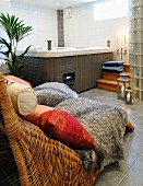 Patterned cushions and sheepskin rugs on comfortable rattan loungers in spa bathroom with whirlpool in corner