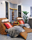 Rattan loungers with cushion and sheepskin blankets in spa bathroom with grey-tiled wall and floor