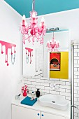 Pink chandelier suspended from light blue ceiling and organically shaped washbasin in feminine bathroom
