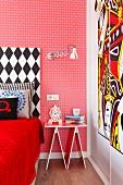 Eklektisches Schlafzimmer mit roter Mustertapete und schwarz-weißem Bettkopfteil, dekoratives Nachttischchen und moderner Kunst