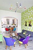 Colourful living area with patterned wallpaper and view into fitted kitchen in retro interior
