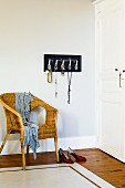 Jewellery rack made from Chinese spoons above wicker chair