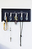 Hand-crafted jewellery rack with Chinese spoons as hooks mounted on wall