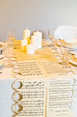 Table runner hand-made from sheet music, white pillar candles and crystal glasses