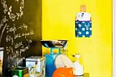 Selbst gebasteltes Wandtasche, als Hängebord aus Schneidebrett und Stoff an gelber Wand aufgehängt