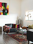 Black leather sofa and glass coffee table on Oriental rug in minimalist interior