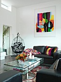 Black leather sofa set and glass coffee table in living room with modern artwork on wall