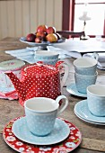 Rustic, red and blue polka-dot teacups and teapot