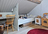Simple, child's bedroom in attic with little boy in bed below sloping, wood-clad ceiling and partition between bed and desk
