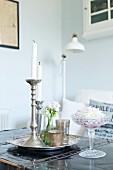 Silber Kerzenhalter mit weissen Kerzen auf Tablett und Kristallschale mit weisser Blüte