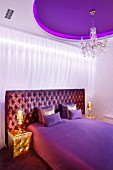 Elegant bedroom in shades of purple, gold bedside lamps on gold pouffes, purple ceiling panel and crystal chandelier