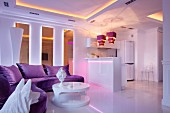 Purple sofa and white, round, designer coffee table in open-plan interior with atmospheric lighting