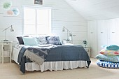 Double bed with grey patterned bedspreads in wood-clad attic room