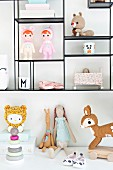 Various fabric dolly and toys on display shelves and cabinet
