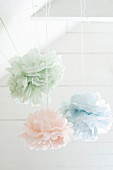 Pastel fabric flowers hung from white-painted wooden ceiling