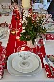 Gedeckter Tisch mit Weihnachtsdekoration und brennenden Windlichtern