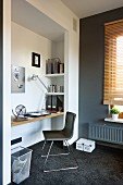 Designer chair at floating desk in niche with grey-painted wall to one side