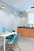 Classic chairs with blue shell seats around breakfast table and Tolomeo sconce lamps on panelled wall in kitchen with geometric, tiled floor