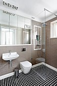 Designer bathroom with flush-fitting, mirrored cabinet, floor-level shower with glass partition and geometric, tiled floor