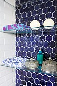 Bathing utensils and Moroccan caskets on glass shelves in niche with blue honeycomb tiles