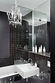 Kleiner Kronleuchter in Designerbad mit schwarzen Mosaiksteinen