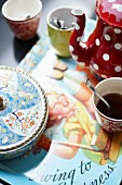 Various beakers, spotted red coffee pot and Chinese china box on place mat with fifties-style picture of child