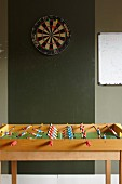 Dartboard on dark green wall behind table football set