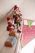 Row of gnomes on shelf on wood-clad sloping wall, colourful bunting and floral pattern in background
