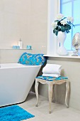 Designer bathtub in bathroom with window, beige tiles, romantic accessories and azure blue, floral devoré textiles